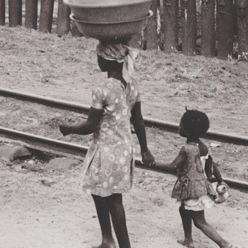 Mãe e filha junto à linha de comboio